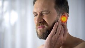 L'uomo soffre da mal d'orecchi, otite, problemi di udito, punto indica il dolore, primo piano fotografia stock