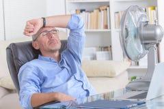 L'uomo soffre dal calore nell'ufficio o a casa Fotografie Stock Libere da Diritti