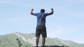 L'uomo solleva le mani sullo stare indietro sul movimento lento superiore di lustro del sole di mattina della montagna video d archivio