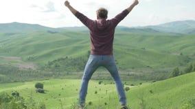 L'uomo solleva le mani sullo stare indietro sulla mattina superiore della montagna stock footage