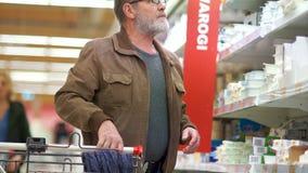 L'uomo solo con una barba grigia sceglie la ricotta dal dipartimento della latteria del supermercato stock footage