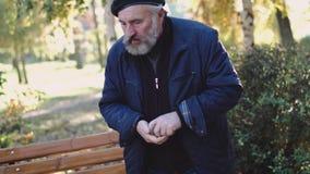 L'uomo solo e invecchiato inghiotte le pillole e si siede sul banco della via archivi video