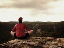 L'uomo solo sta facendo la posa di yoga sulle rocce alza nella mattina nebbiosa Yoga di pratica dell'uomo di mezza età Fotografia Stock