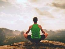 L'uomo solo sta facendo la posa di yoga sulle rocce alza nella mattina nebbiosa Yoga di pratica dell'uomo di mezza età Fotografia Stock Libera da Diritti