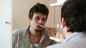 L'uomo sonnolento torturato con i postumi di una sbornia che hanno svegliato appena la spazzola i suoi denti, esamina la sua rifl stock footage