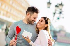 L'uomo sorprende la donna con un regalo Immagini Stock Libere da Diritti