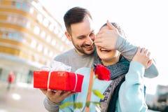 L'uomo sorprende la donna con un regalo Fotografia Stock
