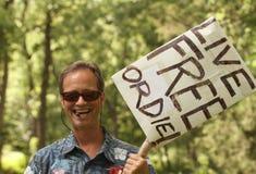 L'uomo sorride con Live Free o muore segno a raduno del ricevimento pomeridiano Fotografie Stock Libere da Diritti