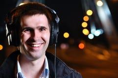 L'uomo sorridente è musica d'ascolto Fotografia Stock Libera da Diritti