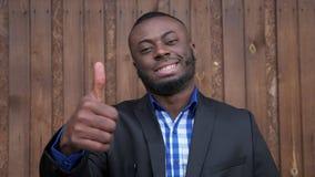 L'uomo sorridente afroamericano nero mostra il pollice di gesto su su fondo di legno scuro archivi video