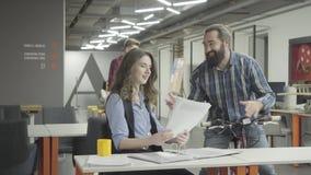 L'uomo sorridente barbuto guida la sua bici con le carte a disposizione e mostra i documenti alla signora nell'ufficio Donna graz video d archivio