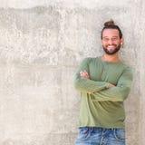 L'uomo sorridente con le armi ha attraversato la tendenza contro la parete Fotografia Stock Libera da Diritti