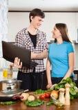 L'uomo sorridente mostra la nuova ricetta alla ragazza Immagini Stock