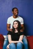 L'uomo sorridente nero e la donna felice si siedono sullo strato fotografia stock