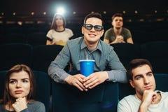 L'uomo sorridente in vetri 3d tiene la bevanda in cinema Fotografie Stock Libere da Diritti