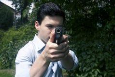 L'uomo spara una pistola ad un obiettivo Fotografia Stock
