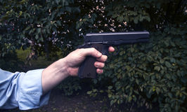 L'uomo spara una pistola ad un obiettivo Fotografie Stock
