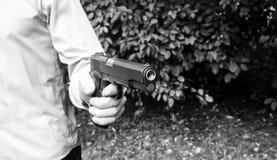 L'uomo spara una pistola ad un obiettivo Fotografia Stock Libera da Diritti