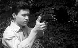 L'uomo spara una pistola ad un obiettivo Immagini Stock
