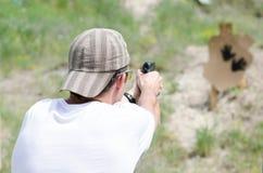 L'uomo spara una pistola alla gamma di fucilazione Immagine Stock