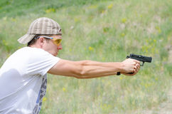 L'uomo spara una pistola alla gamma di fucilazione Fotografia Stock