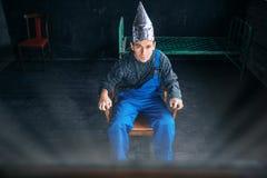 L'uomo spaventato in cappello del di alluminio si siede in sedia Fotografie Stock Libere da Diritti