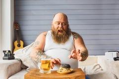L'uomo spesso avido vuole mangiare gli alimenti industriali Fotografia Stock