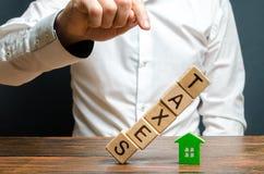 L'uomo spinge la torre dei cubi con le tasse di parola sulla figura della casa Onere fiscale pesanti, mancanza di liquidità fotografie stock libere da diritti
