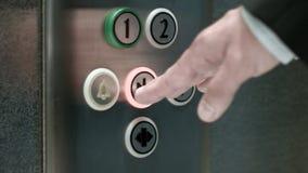 L'uomo spinge le porte di chiusura di un elevatore del bottone video d archivio