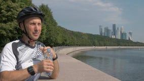 L'uomo in sport uniforme, casco della bicicletta, beve l'acqua da una bottiglia di plastica video d archivio