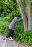 L'uomo sportivo che fa l'allungamento si esercita nella foresta su un albero Immagine Stock