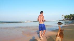 L'uomo sportivo funziona con il cane lungo il movimento lento della linea costiera video d archivio