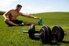 L'uomo sportivo sta esercitando la flessibilità in parco Fotografie Stock Libere da Diritti