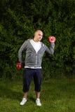 L'uomo sportivo sta esercitandosi con le teste di legno 5kg all'aperto su un verde Immagine Stock