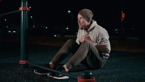L'uomo sportivo sta preparando i suoi muscoli addominali in aria aperta nella notte archivi video