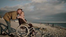 L'uomo sta abbracciando la sua moglie che si siede in trasporto invalido sull'argine del mare video d archivio