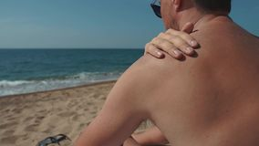 L'uomo sta applicando la crema della protezione solare nella sua pelle, sedentesi su una spiaggia nel giorno di estate stock footage