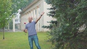 L'uomo sta aspettando la sua ragazza per incontrare una rosa e una mano d'ondeggiamento del hisr Riunione felice stock footage