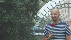L'uomo sta aspettando la sua ragazza per incontrare una rosa e una mano d'ondeggiamento del hisr Riunione felice archivi video