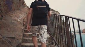 L'uomo sta aumentando delle scale di pietra della scogliera nel posto turistico nella sera, vista posteriore video d archivio