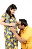 L'uomo sta baciando la pancia della sua moglie incinta immagini stock libere da diritti