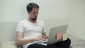 L'uomo sta chiacchierando in siti internet, facendo uso del computer portatile, sedentesi nella camera da letto video d archivio