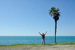L'uomo sta con le sue mani su davanti ad una palma alta su un fondo del mare e del cielo blu Fotografie Stock Libere da Diritti