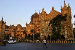 L'uomo sta correndo attraverso una strada vicino alla stazione ferroviaria Victoria Terminus di Chhatrapati Shivaji Terminus Fotografia Stock