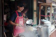 L'uomo sta cucinando la tagliatella ordinaria in Talad-Nam della Tailandia immagine stock