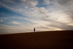 L'uomo sta da solo in cima ad una duna in Sahara Desert Immagine Stock