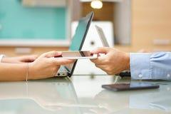L'uomo sta dando il telefono cellulare astuto alla donna accanto ai computer portatili, overu Fotografie Stock Libere da Diritti