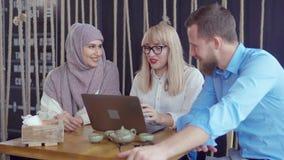 L'uomo sta dicendo a storia di divertimento i suoi due amici femminili in caffè, ridente insieme video d archivio