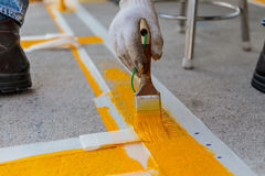 L'uomo sta dipingendo la strada cementata Fotografia Stock