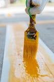 L'uomo sta dipingendo la strada cementata Immagini Stock